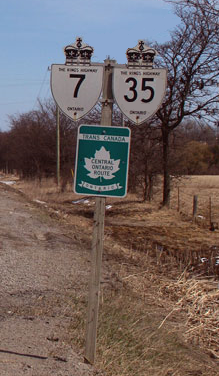 """An image of a signpost on a clear winter day. Behind the signpost are several leafless trees. To the left of the foot of the sign is the gravel shoulder of the road (not pictured) that it stands beside. The signpost is wooden, with three signs. Two are at the top, and one is centred below those. The top two are bullet-shaped signs with a king's crown on top. One is for Highway 7 and one for Highway 35. The sign below is green, with a white maple leaf in the centre. Above the leaf is a white banner with green text, reading ""TRANS-CANADA HIGHWAY"". The centre of the leaf reads in green ""CENTRAL ONTARIO ROUTE"". Finally, a white banner with a hung appearance is below the leaf. The green text within the banner reads ""ONTARIO"""""