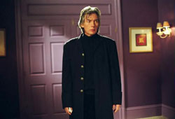 A man dressed in black stands in the middle of a room, he has grey hair.