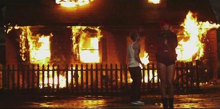 Rihanna and Eminem are standing in front of a burning house in a dark setting.