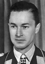 Black-and-white photograph showing the face and shoulders of a young man in uniform. His hair appears dark and is combed to the back. The front of his shirt collar bears an Iron Cross decorations, black with light outline. He is looking at to right of the camera, his facial expression is determined.