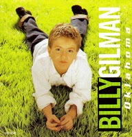 A sunlit grass field shows Billy Gilman on his stomach with his legs up and hands in front of him.