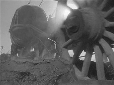 A wooden wagon wheel with 16 spokes occupies the right half of the image; the camera was perhaps 3 or 4 feet from this wheel. The wheel is biting about 6 inches into loose soil. Rays of sunlight are coming through just a few of the upper spokes, and are readily visible in the dusty air. The left half of the image shows the back side of a horse in harness that is straining to pull the wagon.