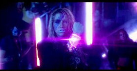 Kesha deflecting a laser beam shot from Star in the music video's choreographed dance battle sequence. The video is intended to look 80s themed with inspiration drawing from movies of that time.
