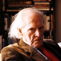 Photographic portrait of an unsmiling, elderly man looking side on into camera. The hair he has is white and collar length. He wears a brown jacket, blue collared shirt and red tie. He appears to be seated and in front of a bookcase.
