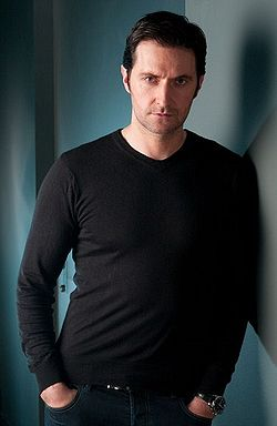 A serious looking dark haired man in his late thirties wearing a black t-shirt, and leaning against the wall
