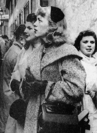 Picture of a woman standing in a crowded street, looking away from the camera