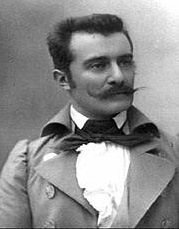 Monochrome head and shoulders photographic portrait of a man with a mustache and short dark hair, face turned slightly to his left, wearing a jacket, high-collared shirt, and loose bow tie