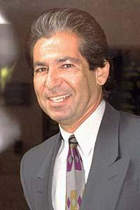Robert Kardashian smiles at the camera, dressed in a suit