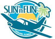 "Logo depicts a small plane flying towards the viewer and facing the left. The background consists of two concentric circles (inner is yellow depicting the sun, outer is light blue to represent the sky). On the right is a palm tree and on the left (above the plane) is the name ""SUN 'n FUN""."