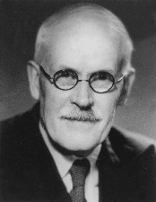 Black and white portrait photograph of Sir Harold Jeffreys looking into the camera. He is wearing a shirt, tie and jacket. He has a moustache and is wearing spectacles.
