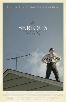A man standing on the roof of a house, looking off to his left. His hands are on his hips. Behind him is a TV aerial.