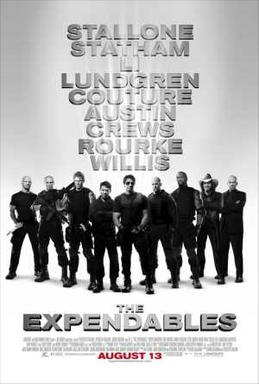 Nine armed men dressed in black standing shoulder to shoulder, Sylvester Stallone front and center.