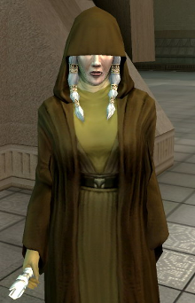 An elderly woman, Kreia, stands, wearing earth-tone robes. The top half of her face, along with her eyes, are covered by dark brown hood, part of another robe worn over her clothes. A braid of hair comes down from each side of her face, and her left hand is missing.