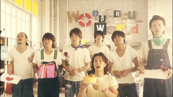 Seven men stand dejectedly while holding gifts for a woman.