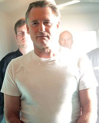 Oswald Danes, dressed in a plain white T-shirt, being accompanied from his prison cell