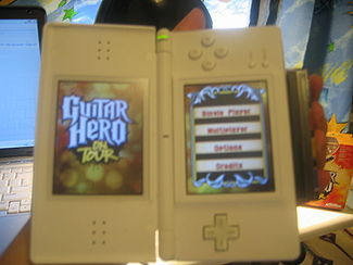 "The ""Guitar Grip"", developed by Vicarious Visions for the Nintendo DS series Guitar Hero: On Tour provides four fret buttons for the game, while strumming is done on the DS touchscreen by use of a pick-shaped stylus. Holding GHOT front.jpg"