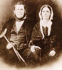 John Crenshaw, a notorious illegal slave trader, holding a crutch, with his wife, Francine