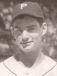 "A black-and-white image of a young man in his teens shown from the shoulders up, wearing a white baseball jersey with white buttons and a baseball cap with a white block ""P"" on the front."