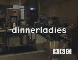 "The BBC logo and the text ""dinnerladies"" in a rounded white font overlayed on the image of a darkened canteen."