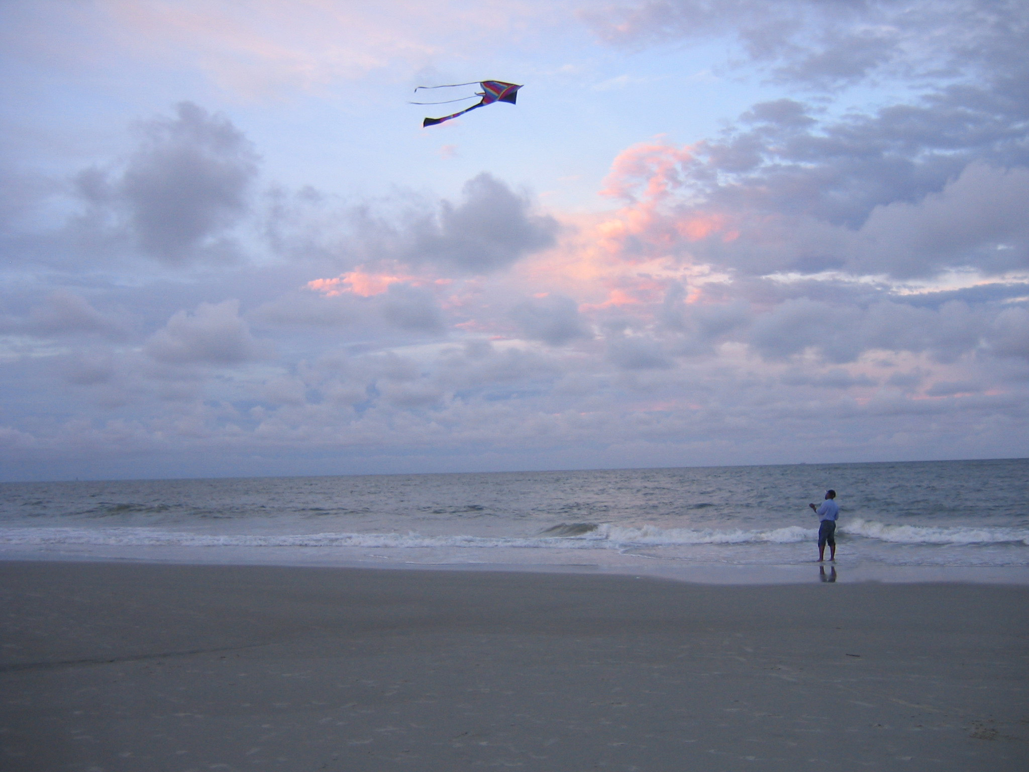 kite a man flying a kite on the beach a good location for flying as winds travelling across the sea contain few up or down draughts which cause kites to fly