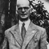 Upper torso of balding, bespectacled man wearing suit with tie.