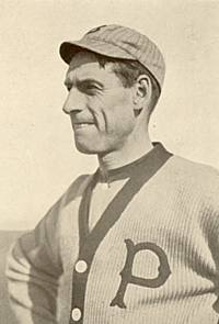 "A sepia-toned image of a man wearing a button-down sweater with a ""P"" on the left breast and a crownless pinstriped baseball cap"