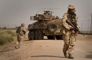 Australian soldiers supported by an ASLAV-25 patrol along a railway line near Camp Smitty during routine foot patrols in Al Muthanna Province