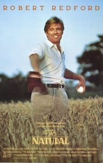 A man (Redford) standing in a field of waist high wheat, with a baseball ready to throw in one hand and a glove on the other