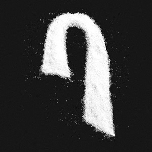 Salt is sprinkled across a black background, forming Max's signature haircut logo. There is no text on the cover.