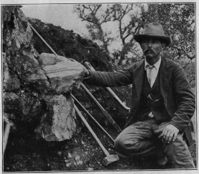 William E. Hidden next to a 73 lb (33 kg) mass of gadolinite in place at Barringer Hill, 1903.