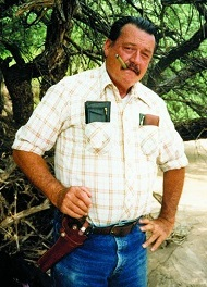 Glenn Boyer standing smoking a cigar with a holstered six-shooter on his hip.