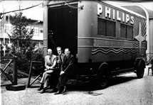 Three men sitting on back of Philips truck