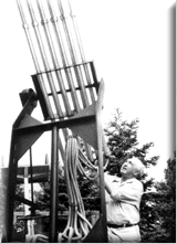 monochorome photograph of a man stood alongside of a device which comprises mainly a series of vertical pipes
