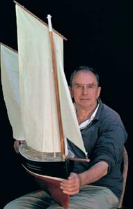 knee high portrait of subject carrying a three-foot sailboat