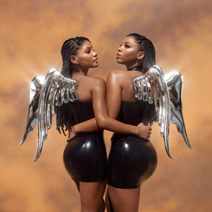 Two females with shiny, metallic wings on their backs, both wearing latex dresses, standing and holding each other by one arm in front of a dusty background