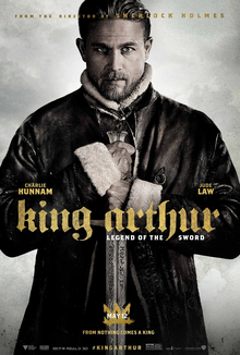 King Arthur wears a leather jacket in front of a pink sky and faces the viewer, his sword held by both hands downward in front of his chest.