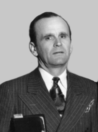 A middle aged man wearing a pinstripe suit with a tie