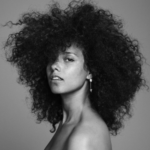 The black and white picture shows woman with black curly hair, wearing a silver earring and looking straight at camera.