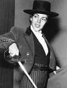 Black and white photograph of a woman wearing a bullfighter's costume, she is holding a sword in one hand and a cape in the other.