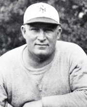 Posed black and white photograph of Owens wearing a grey sweatshirt and a white New York Giants baseball cap