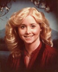 Portrait of Michelle Martinko. She has shoulder-length blonde curly hair and is wearing a red blouse.