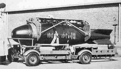 A Red Beard weapon on its bomb trolley, fitted with a bomb carrier prior to loading into an English Electric Canberra bomber.  The two fore and aft vertical plates shown with holes in them were baffles unique to the Canberra installation, designed to reduce airstream buffeting that could tear off the bomb doors.  The baffles were made from 1 in (25 mm) thick marine plywood, drilled with numerous 1 in (25 mm) diameter holes.  The tail fins of the bomb are retracted.