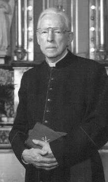 An older man dressed in Roman Catholic priestly garb holds two books in his hands, which he has folded in front of him, and stares at the camera with a neutral look on his face.