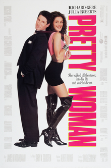 A man in a black smart suit stands back to back with a woman wearing a black short skirt and black thigh-high boots.