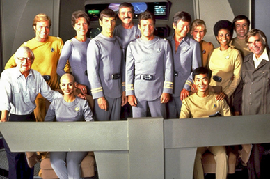 The main cast of The Motion Picture in the film's costumes on the bridge set. Clockwise from far left: director Robert Wise: Collins, Barrett, Nimoy, Doohan, Shatner, Kelley, Whitney, Nichols, Koenig, producer Gene Roddenberry, Takei, and Khambatta. These and other publicity shots were taken after screen tests for the actors on August 3, 1978. St1-cast publicity shot.png