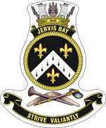 "A ship's badge. A naval crown sits on top of a black scroll with ""JERVIS BAY"" written in gold. This is atop a yellow, rope-patterned ring, which contains a black field. Three gold fleur de lys are positioned at the bottom, upper left, and upper right: the bottom one is separated from the other two by a white chevron containing eight black marks. Below the ring are a stone axe and a nulla nulla sitting on top of a boomerang. At the bottom of the badge is a black scroll with ""STRIVE VALIANTLY"" written."