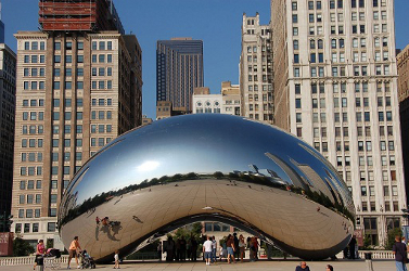 A large, highly-polished, mirrored bean-shaped sculpture seen from the east, reflecting the skyscrapers to the north along East Randolph Street (The Heritage, Smurfit-Stone Building, Two Prudential Plaza, One Prudential Plaza, and Aon Center.