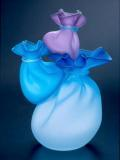 A glass sculpture in three shades of blue resembles a group of satin bags