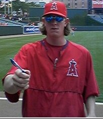 "A white man wearing a red baseball cap and warmup, both with a red ""A"" topped by a halo. The man is holding out his right hand, which is holding a pen, and wearing sunglasses."