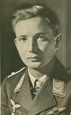 The head and shoulders of a young man, shown in semi-profile. He wears a military uniform with an Iron Cross displayed at the front of his shirt collar.